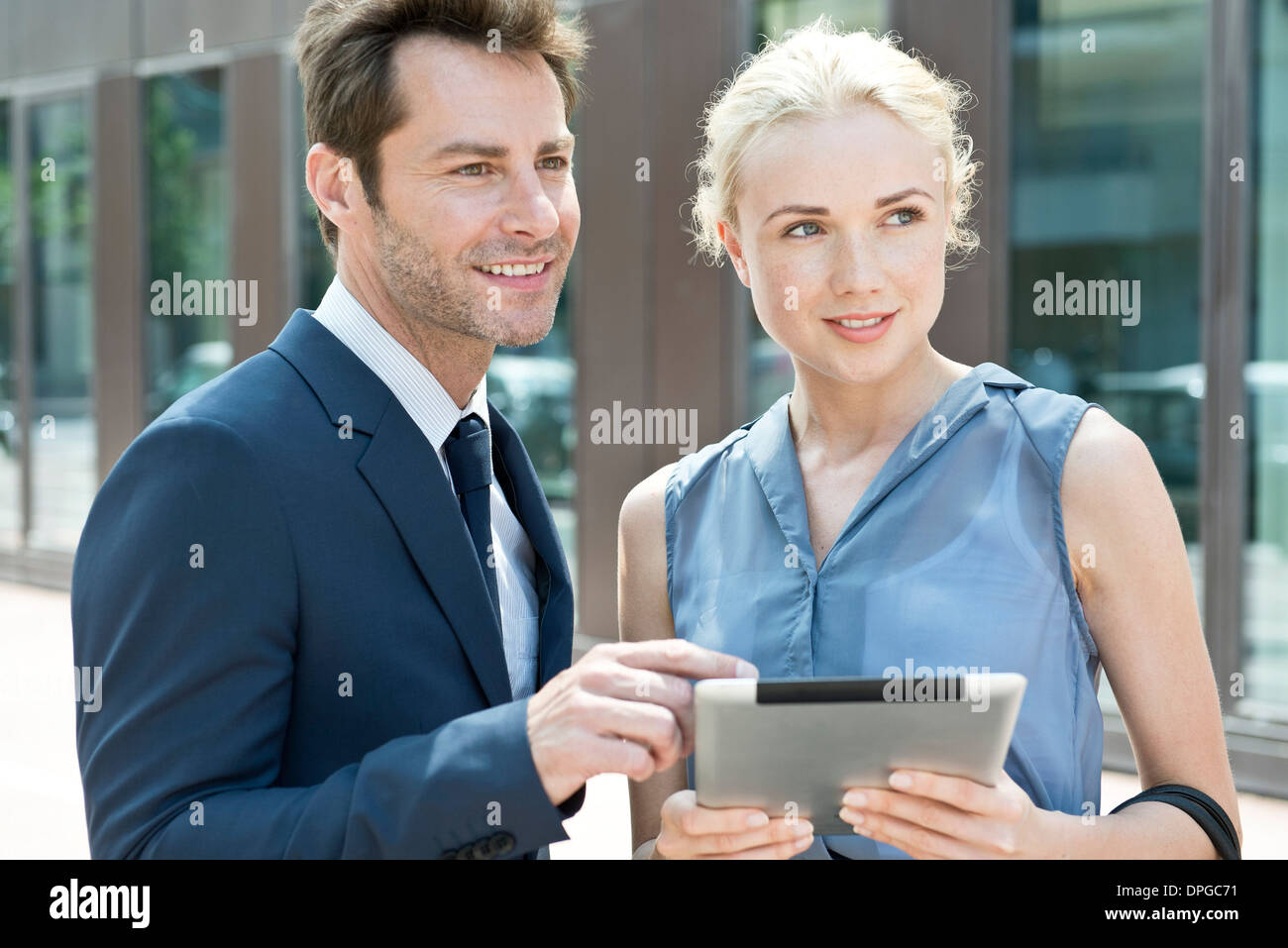 Real estate agent with digital tablet showing property to potential buyer - Stock Image