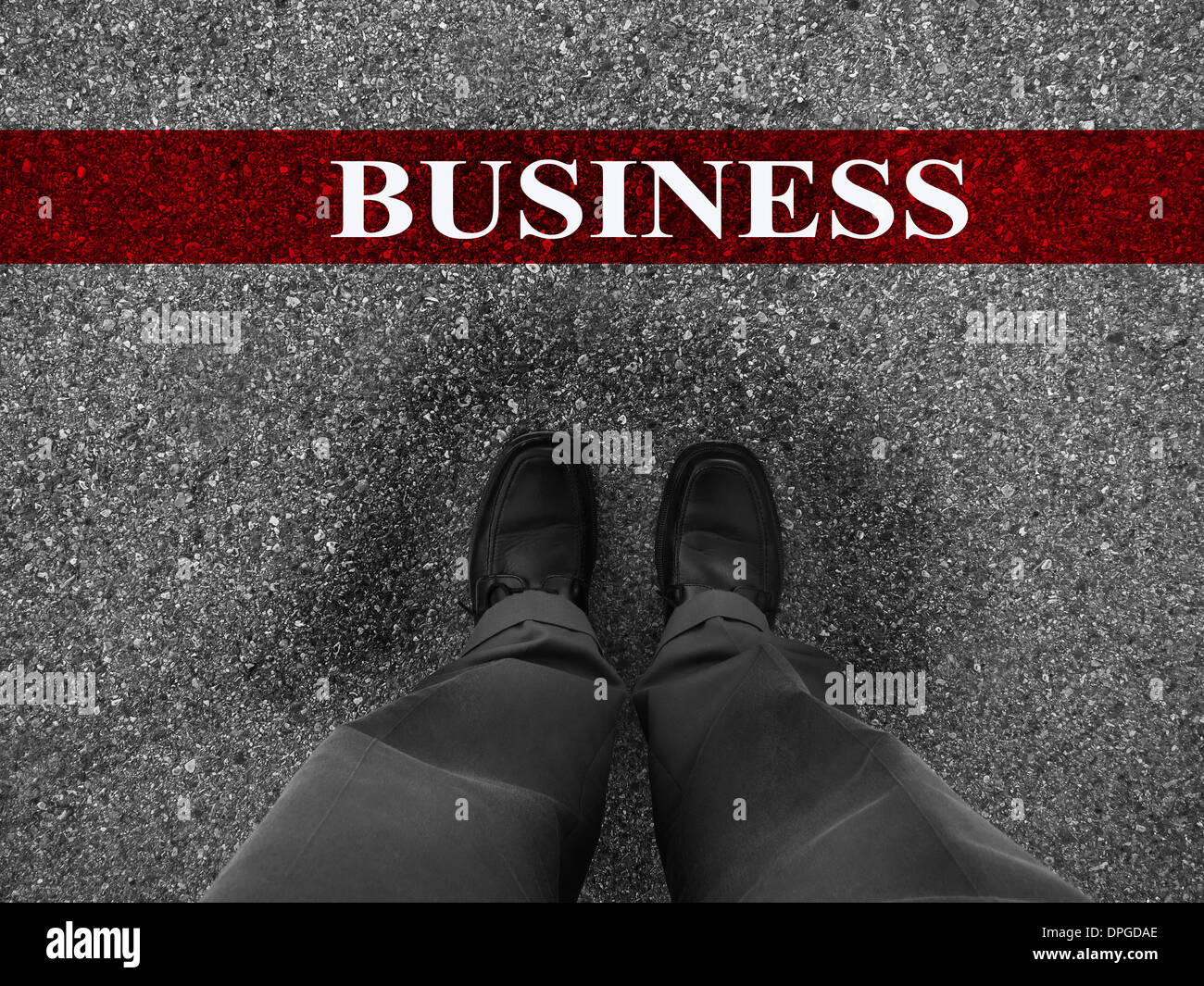Businessman standing on asphalt starting line with motivation word of Business - Stock Image