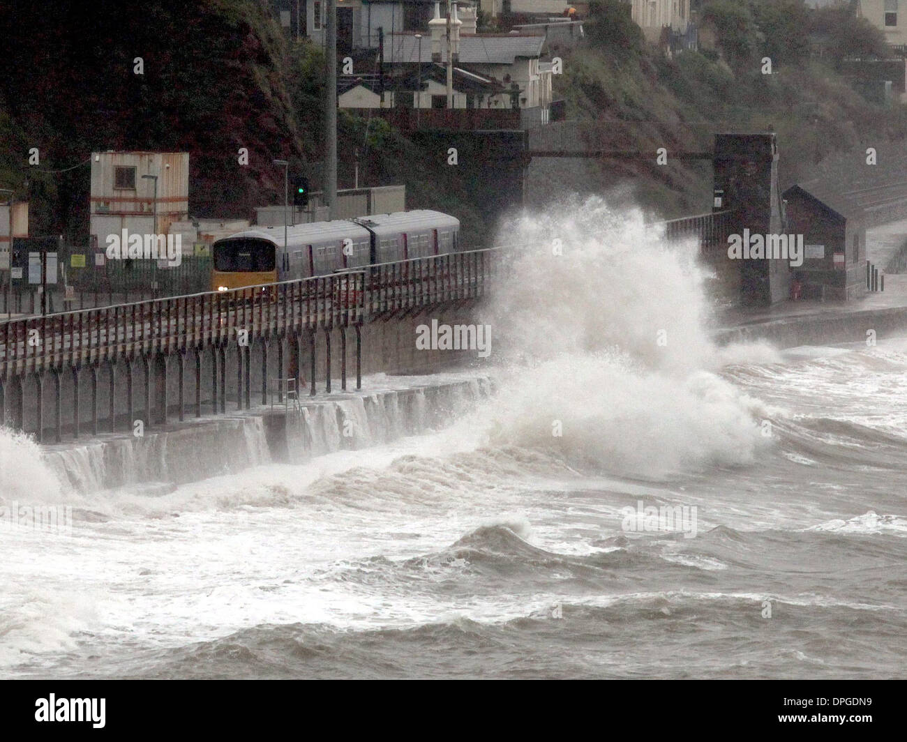 A train is battered by waves as it passes through the Dawlish train station, Devon - Stock Image