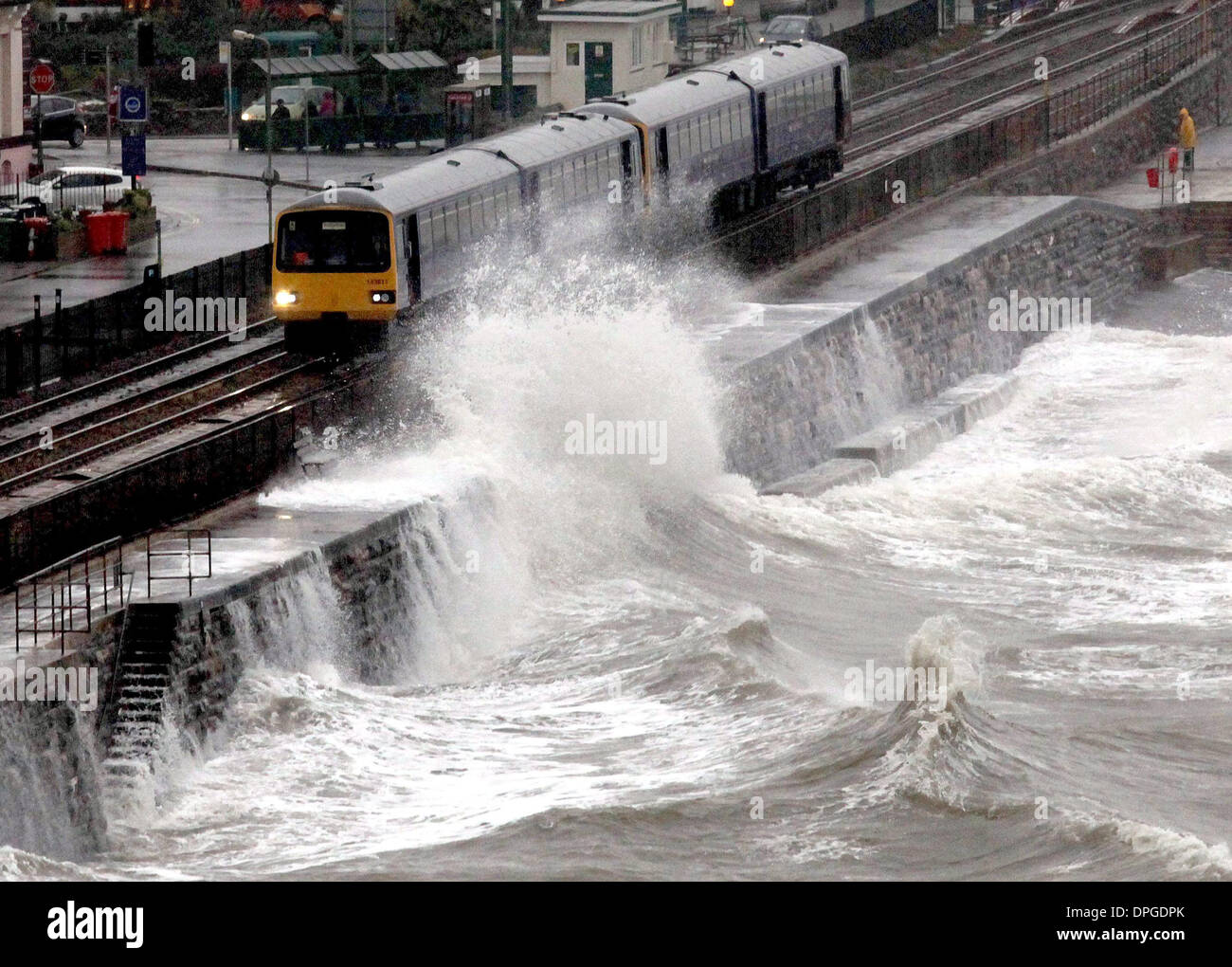 A train is battered by waves as it passes through Dawlish train station Stock Photo