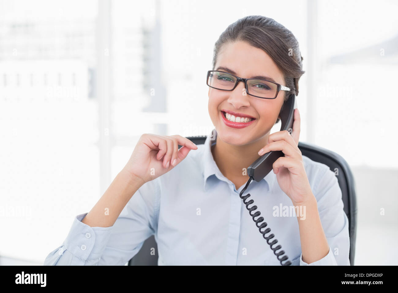 Delighted classy brown haired businesswoman answering the telephone - Stock Image