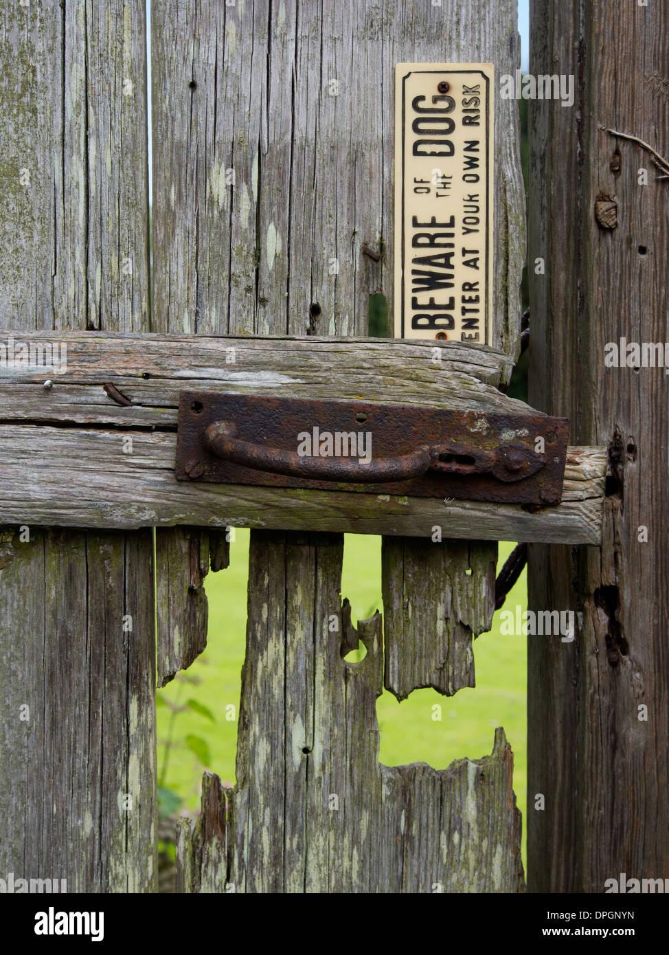 a decrepit old wooden gate warns of a dog long gone - Stock Image