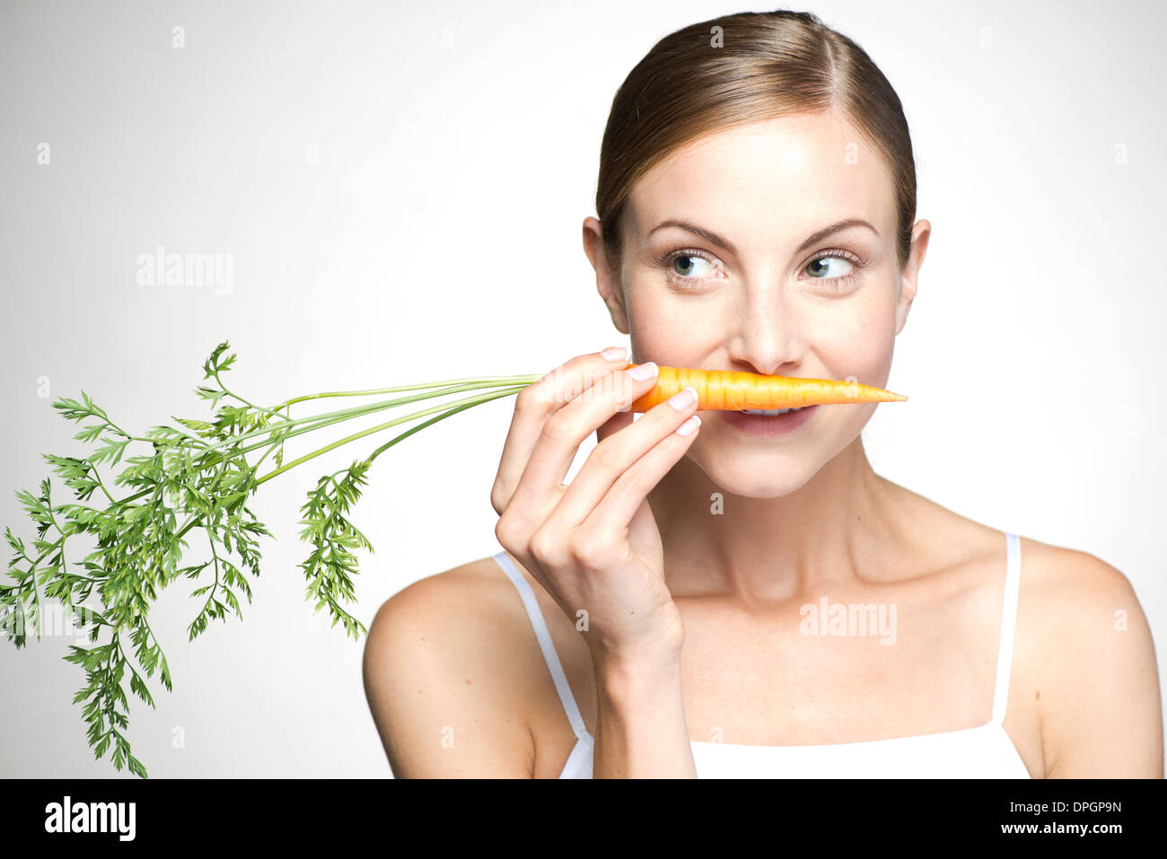 Young woman smelling carrot - Stock Image