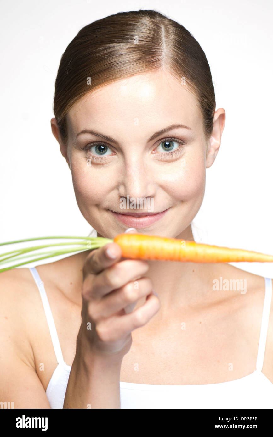 Young woman balancing carrot on hand, portrait - Stock Image