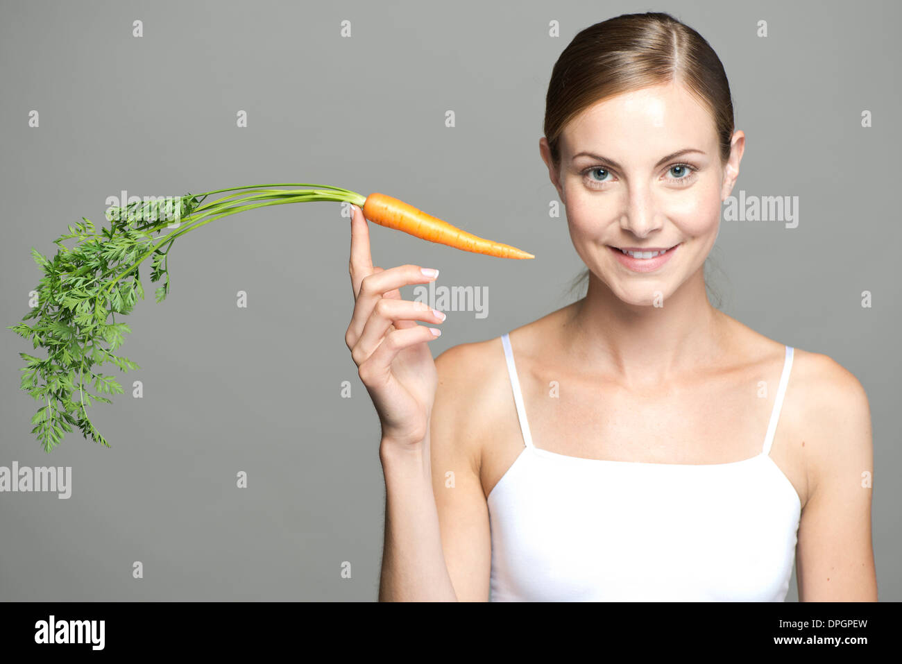 Young woman balancing carrot on fingertip - Stock Image