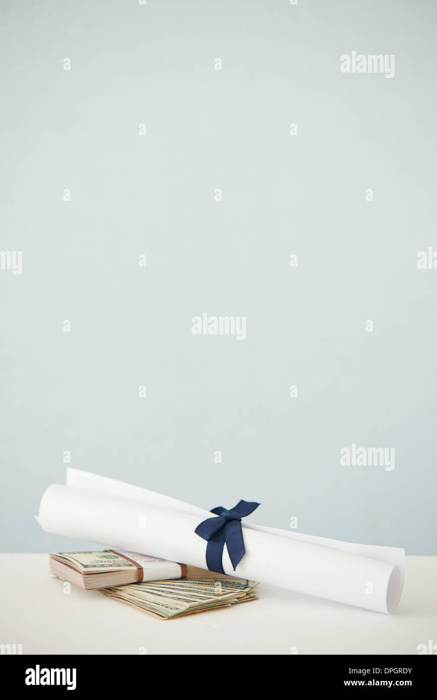 College diploma set atop stacks of cash Stock Photo
