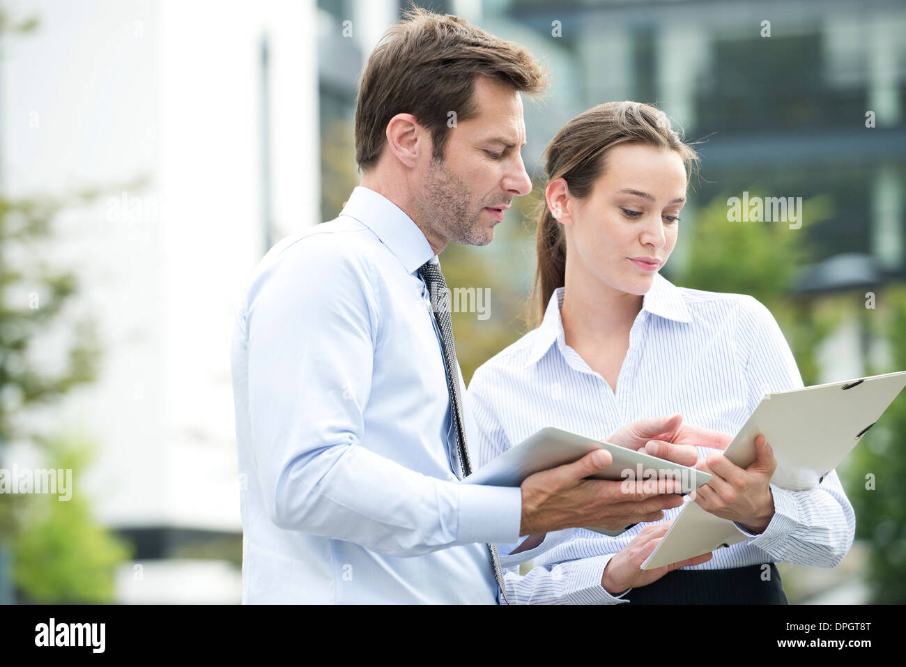 Business associates collaborating using digital tablet - Stock Image