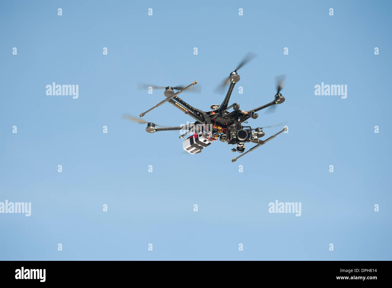 An unmanned Aerial Vehicle (UAV) / drone used for aerial surveillance is flying in the air - Stock Image