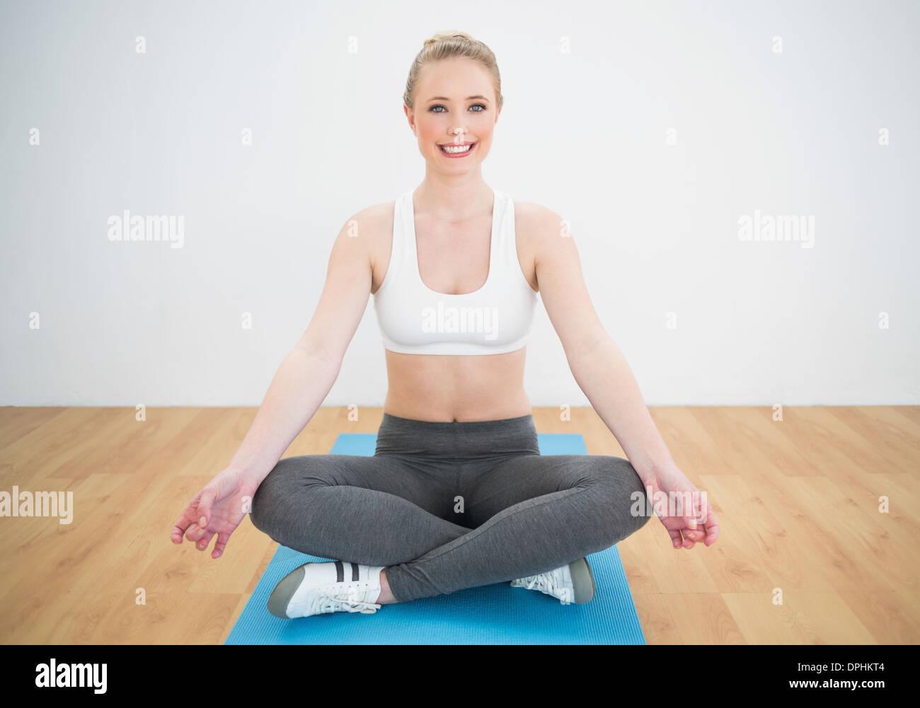 Happy sporty blonde sitting cross legged on exercise mat - Stock Image