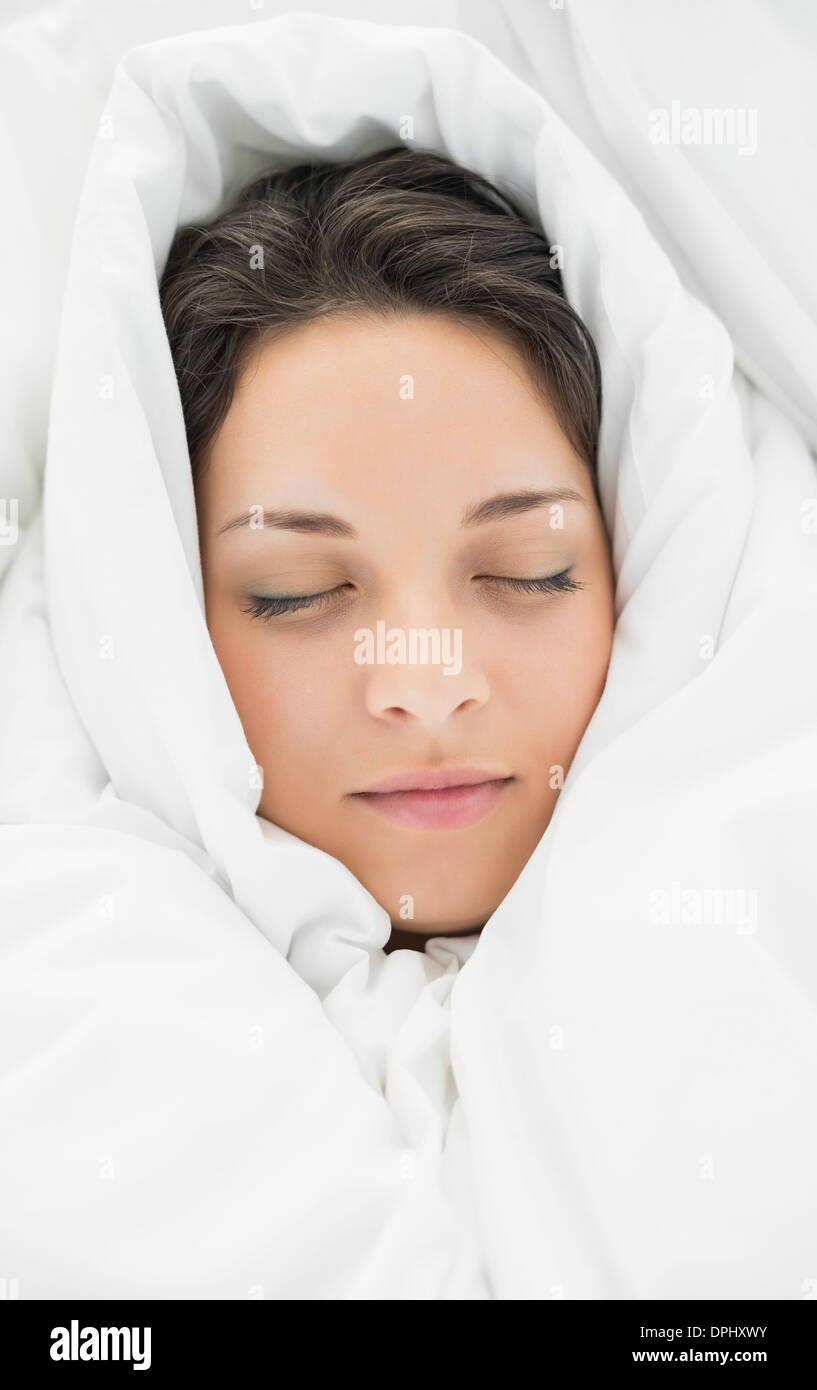Peaceful casual brunette wrapped up in her duvet - Stock Image