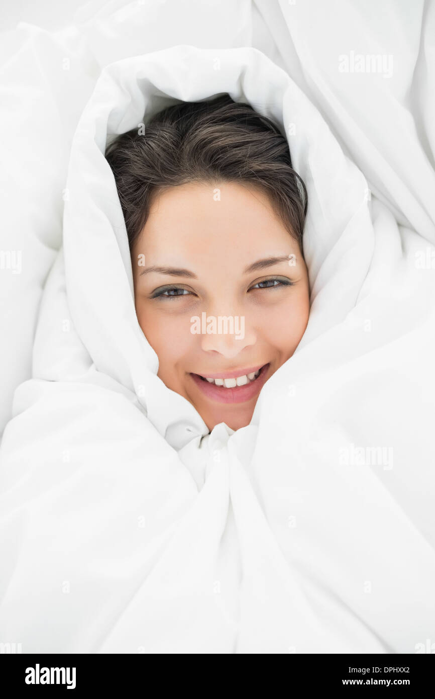 Smiling casual brunette wrapped up in her duvet - Stock Image