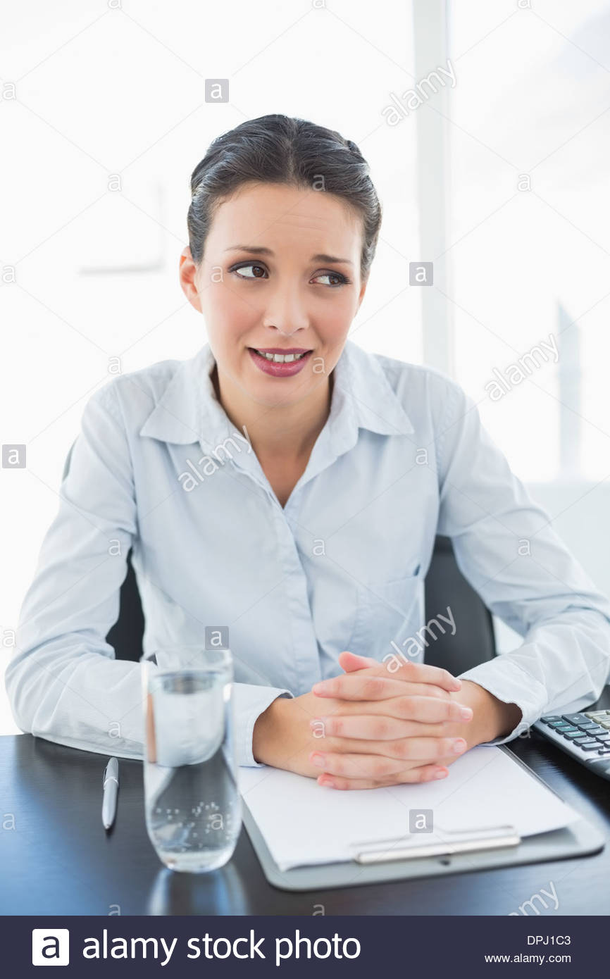 Skeptical stylish brunette businesswoman joining her hands and looking away - Stock Image