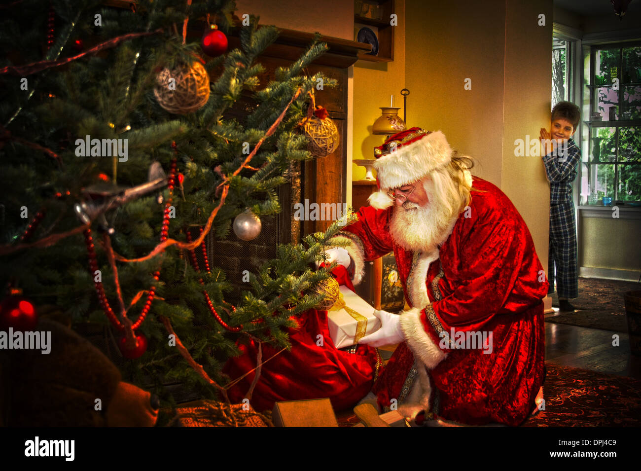 a little boy seeing santa claus putting presents under the christmas tree - Santa Claus With Presents