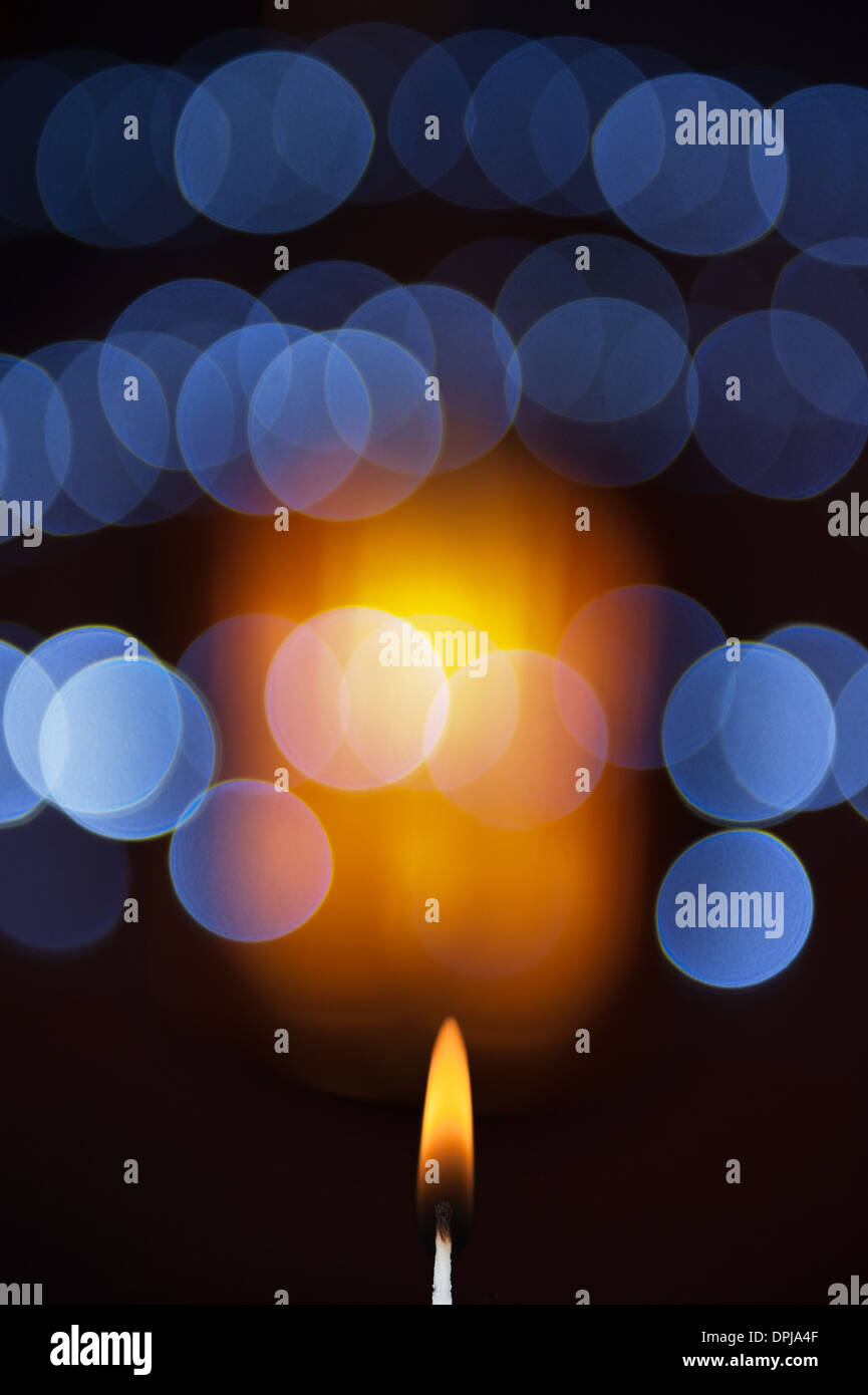 abstract christmas lights bokeh with candle flame - Stock Image
