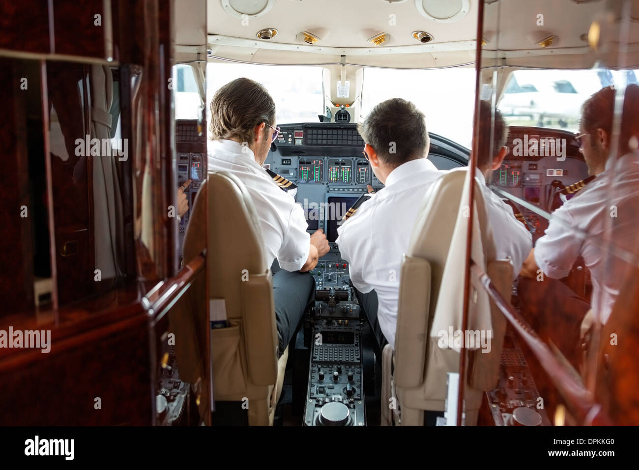 Pilots Operating Controls Of Private Jet - Stock Image