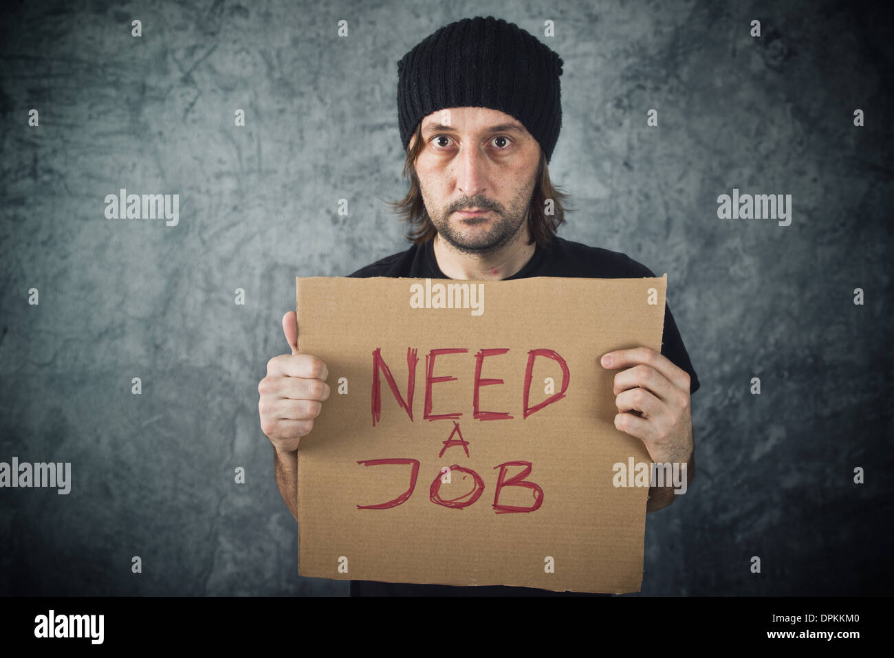 Man holding cardboard paper with Need a Job message. Job seeking, unemployment issues. - Stock Image