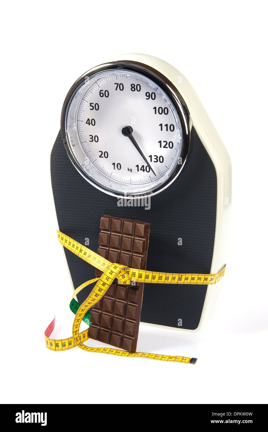 A scale with measuring tape and chocolate - Stock Image
