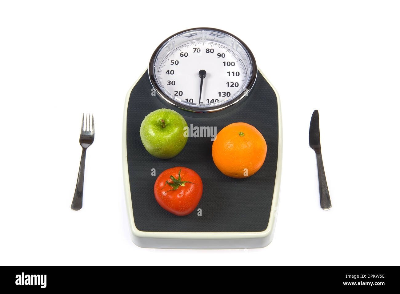 A weight scale with fruit a fork and a knife - Stock Image