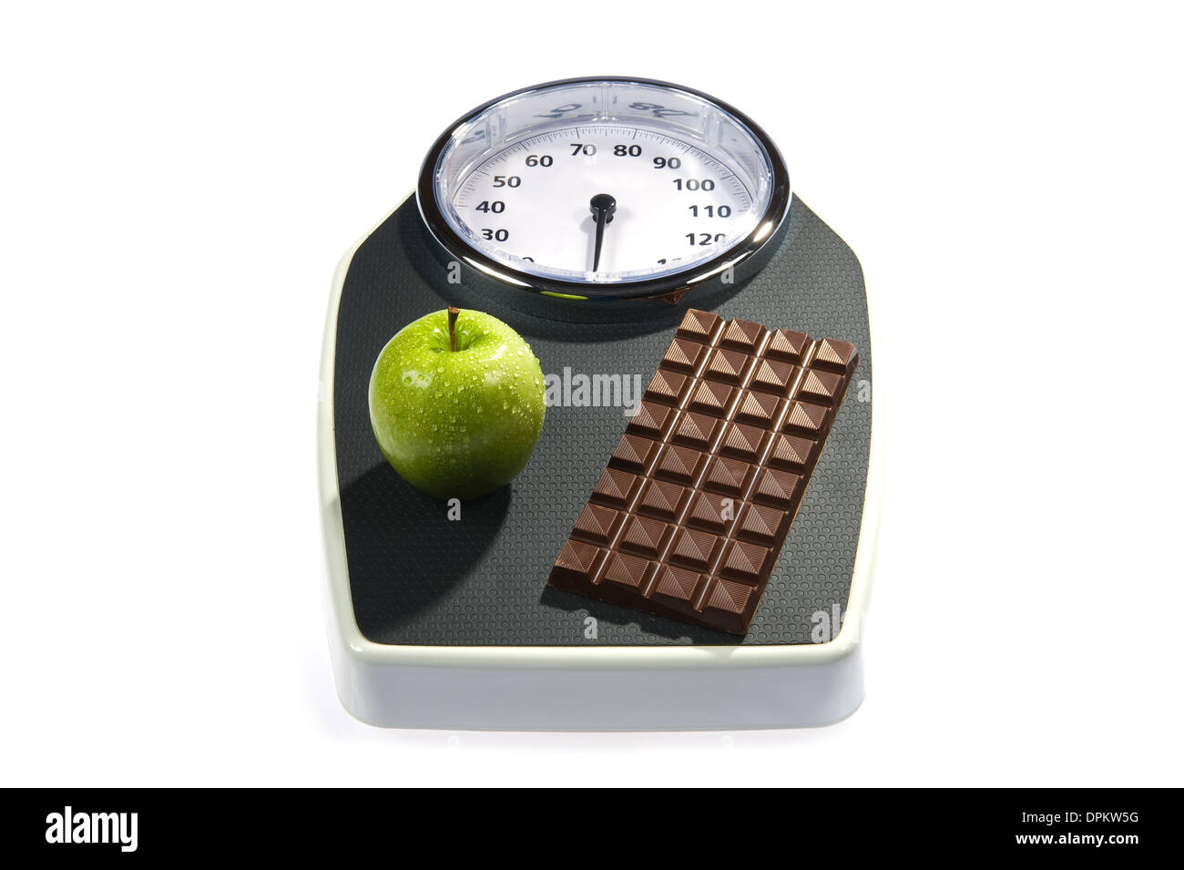A weight scale with chocolate and an apple - Stock Image