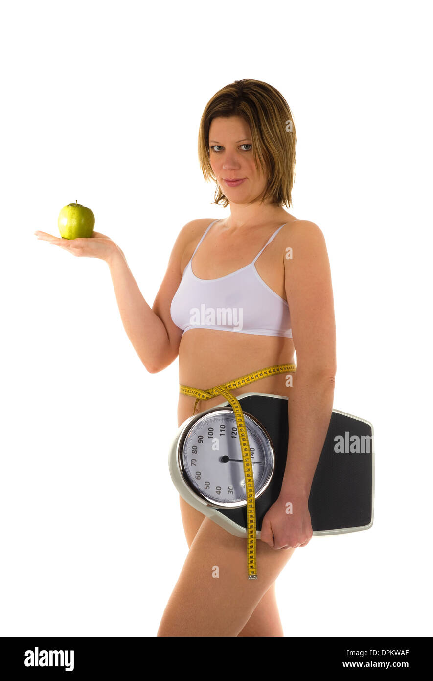 A woman with a weight scale and an apple - Stock Image