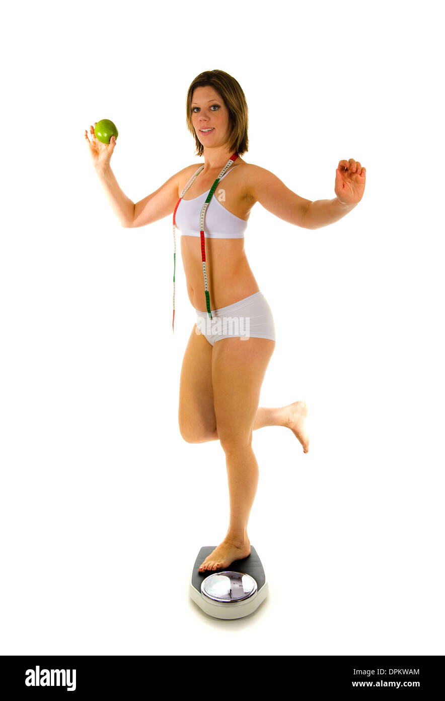A woman standing on a weight scale with an apple - Stock Image