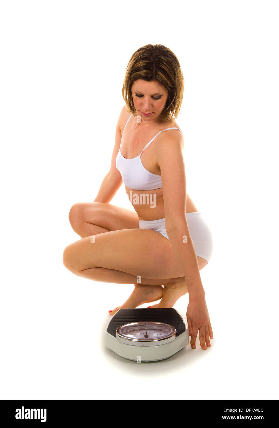 A woman is looking at the clock of her weight scale - Stock Image