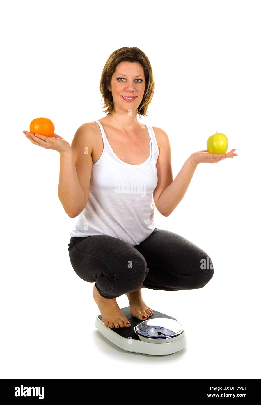 A woman is sitting on a weight scale with fruit - Stock Image