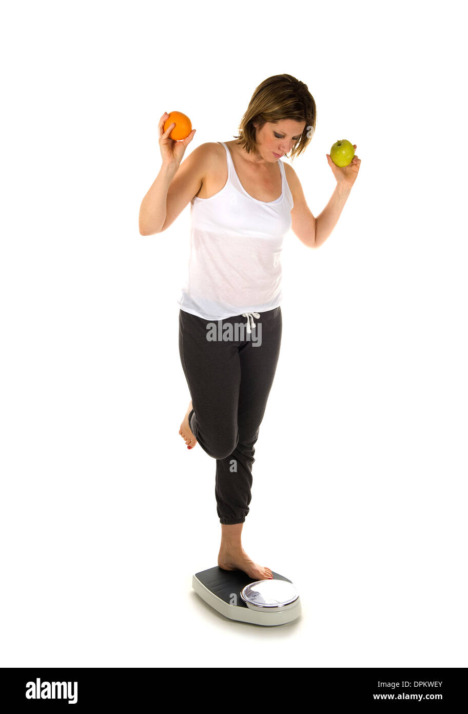 A woman standing on a weight scale with fruit - Stock Image