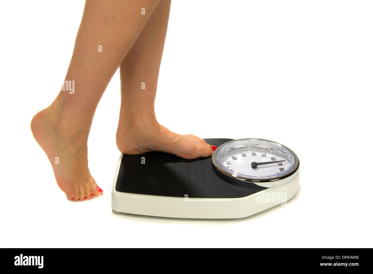 A woman standing on a weight scale - Stock Image