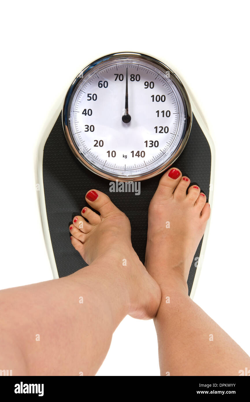 A woman is standing on a weight scale - Stock Image