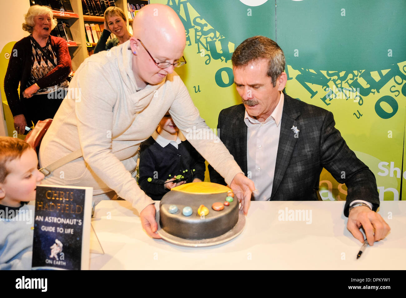 Belfast, Northern Ireland. 14 Jan 2014 -  Commander Chris Hadfield is presented with a 'Solar System Cake' as he signs copies of his book 'An Astronaut's Guide to Life on Earth' Credit:  Stephen Barnes/Alamy Live News - Stock Image