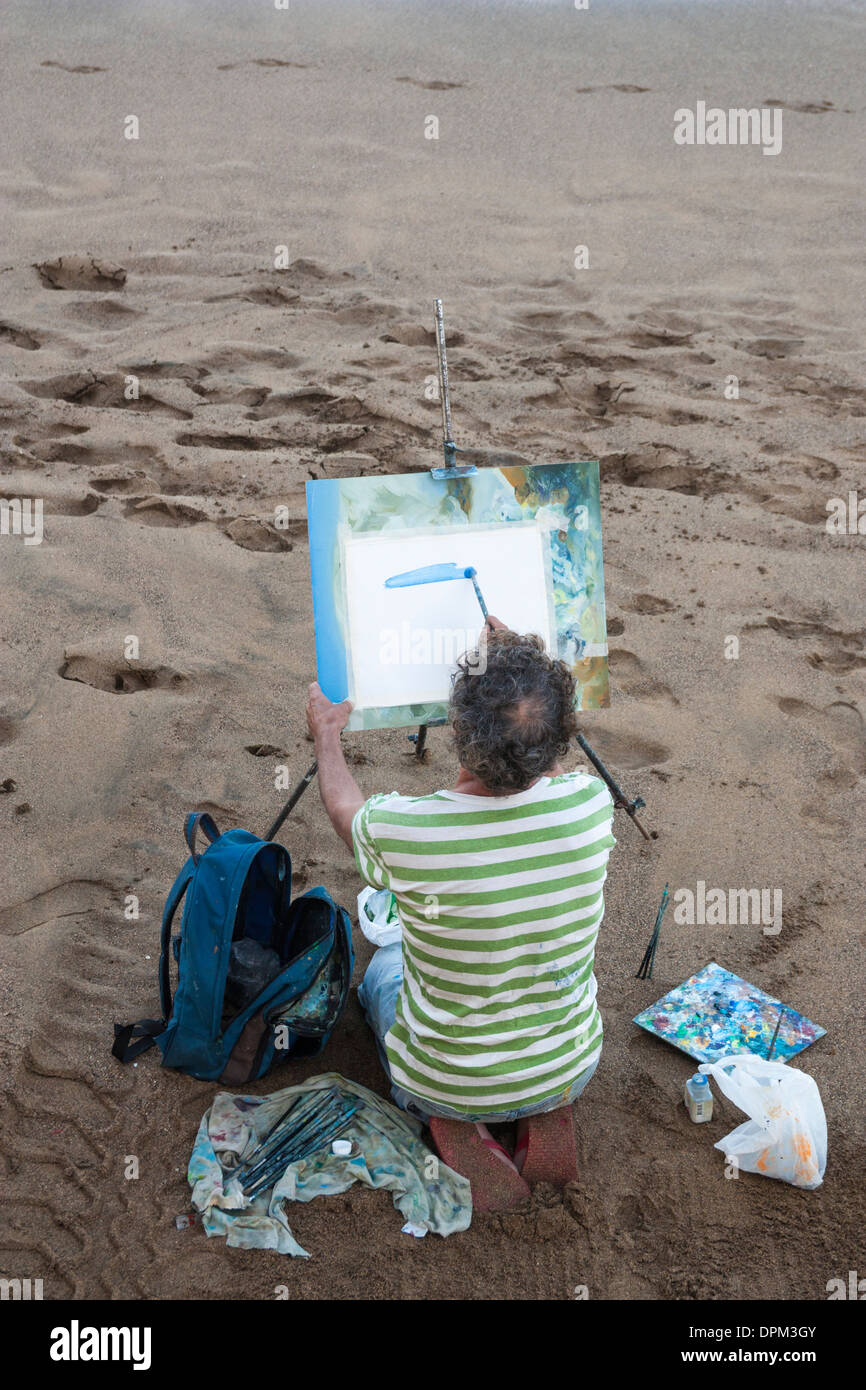 Artist on beach putting first brush stroke on blank canvas with blank canvas - Stock Image