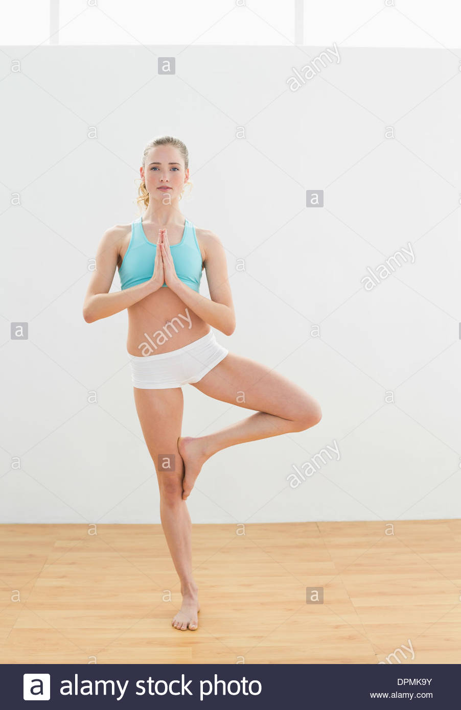 Calm slim blonde standing in eagle pose - Stock Image