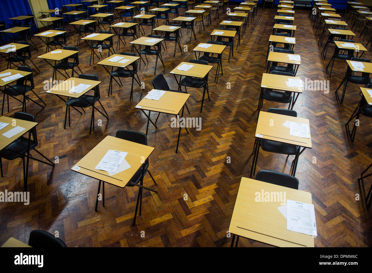 Rows of empty desks ready for Welsh GCSE school pupils to sit their exams in a school hall, Wales UK - Stock Image