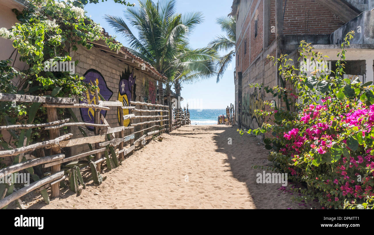 sandy pathway to Pacific coast beach & blue ocean at Zipolite blooming bougainvillea & palms adobe wall rail fence Stock Photo