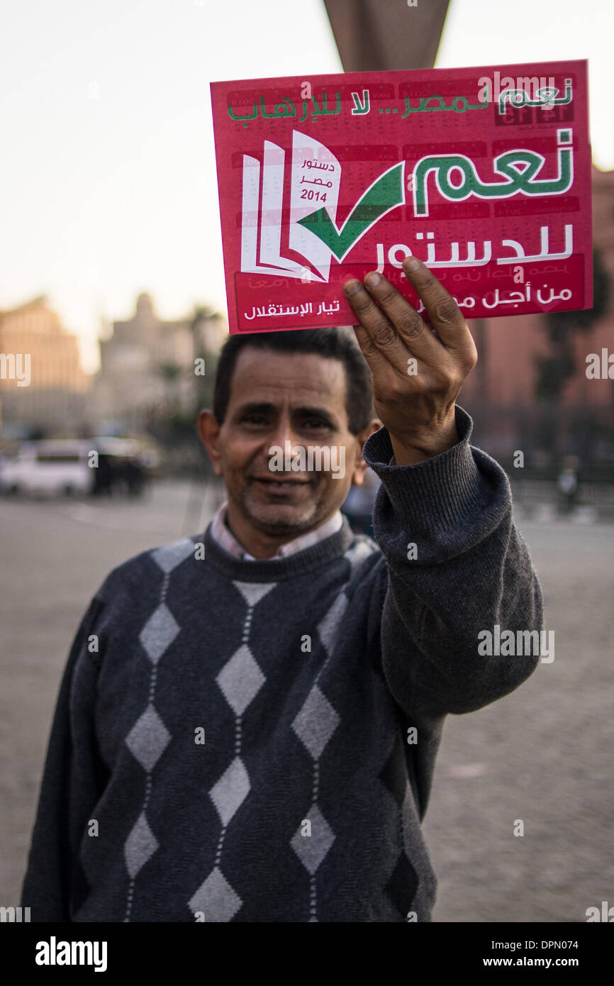 Cairo, Egypt. 15th Jan, 2014. A man holds a card reading 'YES for the new draft constitution' during a demonstration in support of Egyptian army and Defense Minister Abdel Fattah el-Sisi, near closed Tahrir Square in Cairo, capital of Egypt, on Jan. 15, 2014. Egyptians finished Wednesday their two-day voting on the country's new draft constitution, which is widely seen as a milestone in Egypt's political transition after Islamist president Mohamed Morsi was ousted last July. Credit:  Pan Chaoyue/Xinhua/Alamy Live News - Stock Image