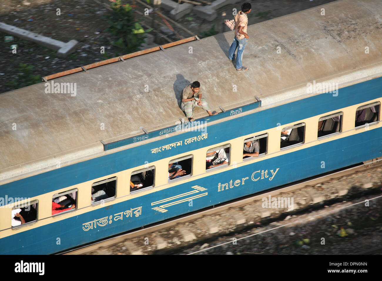 One man standing and another sitting on the roof of a high speed commuting train through the city of Dhaka, Bangladesh - Stock Image