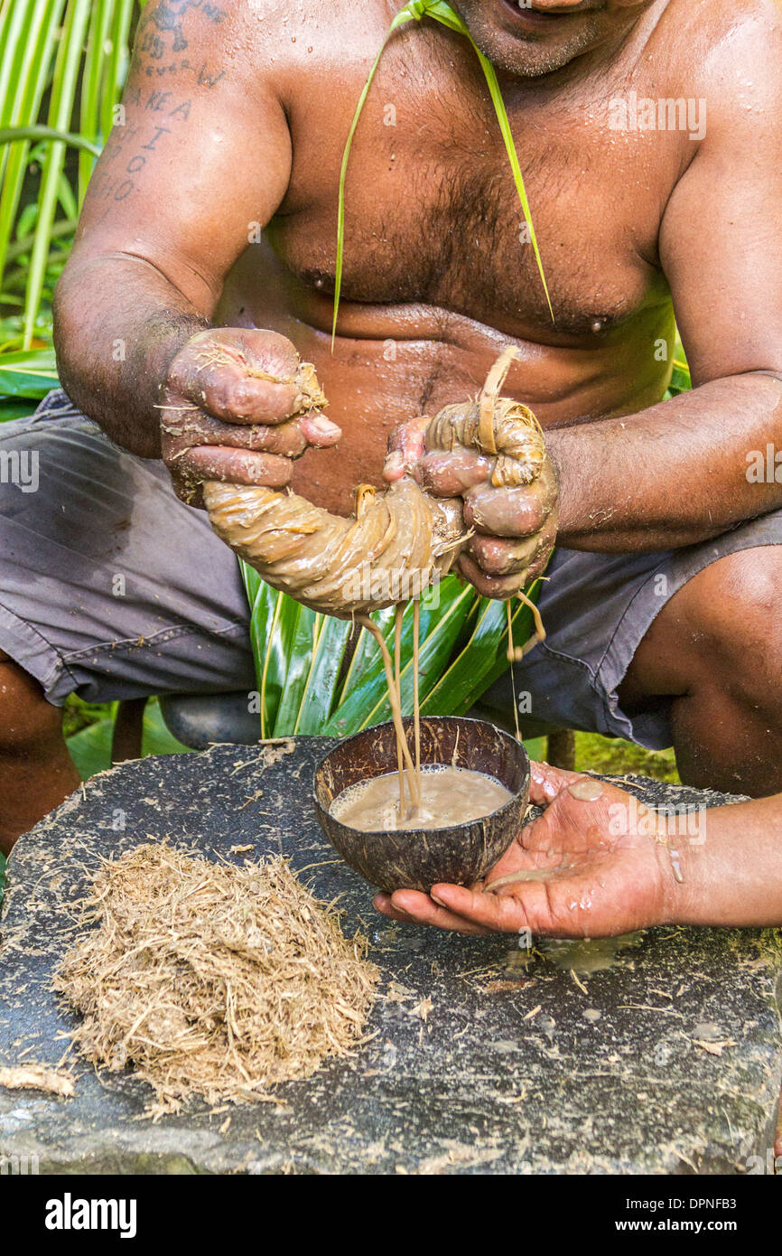 Local man sqeezes bamboo strips with kava root inside to