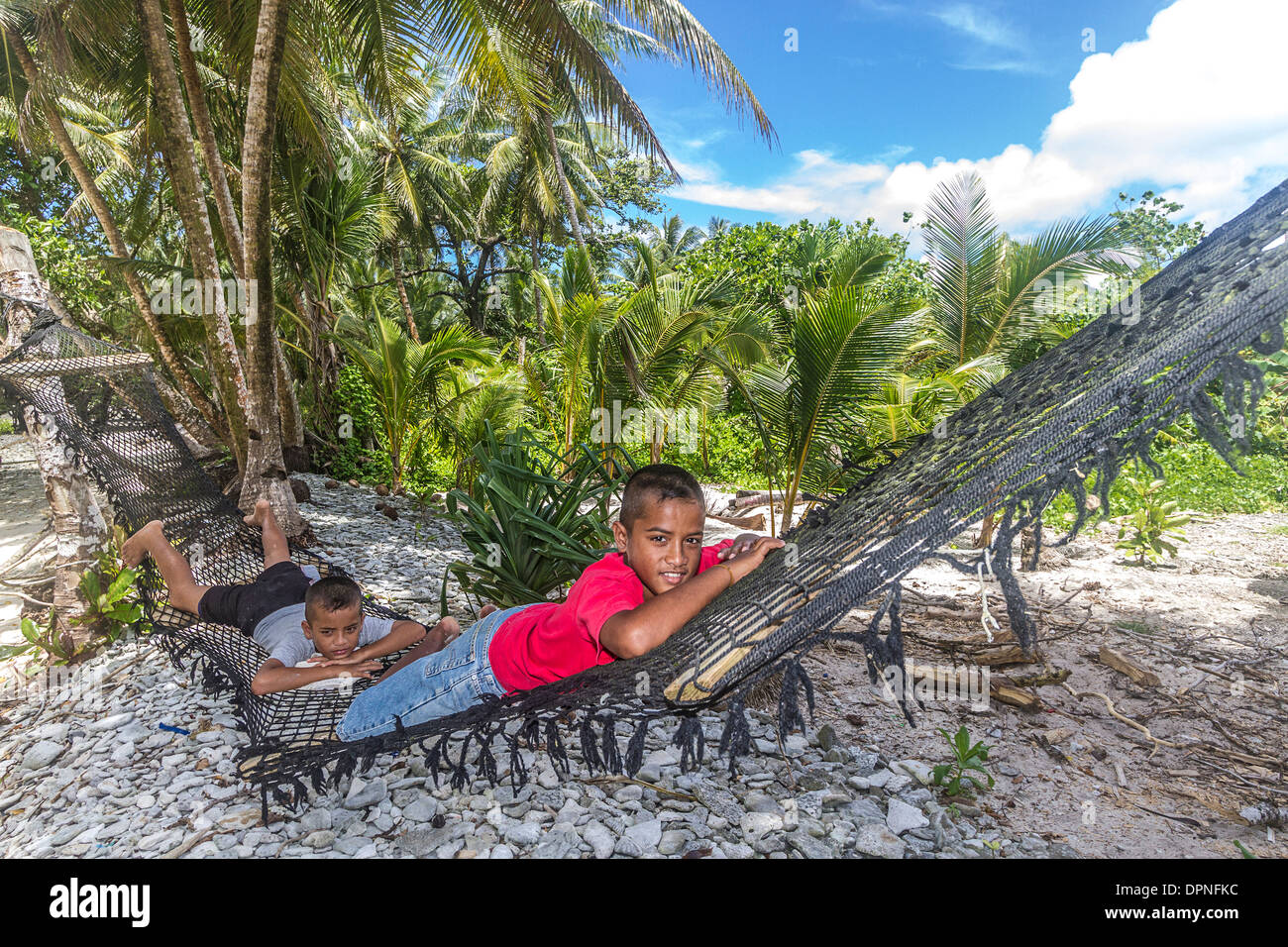 Young local boys lie in a hammock on a beach in Kosrae, Micronesia. - Stock Image