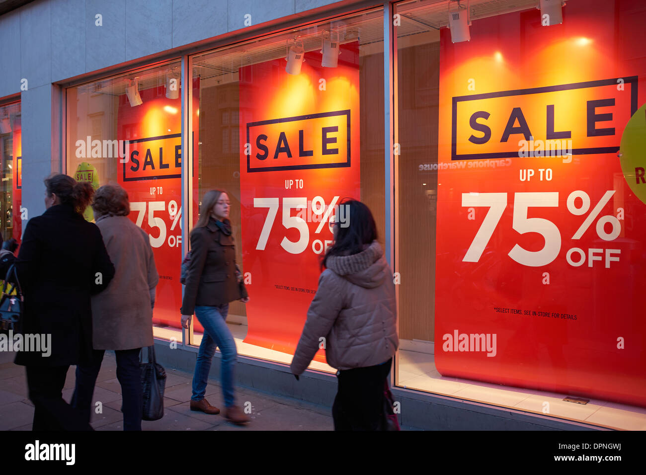 Shoppers walking past the sale banners in a shop window - Stock Image