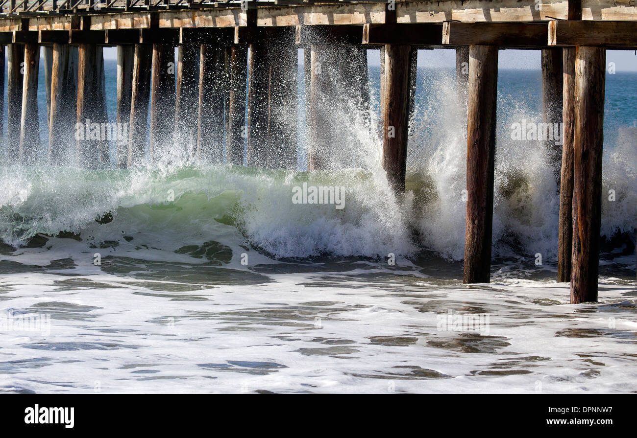 Wave Crashing Against Pier Pillars - Stock Image
