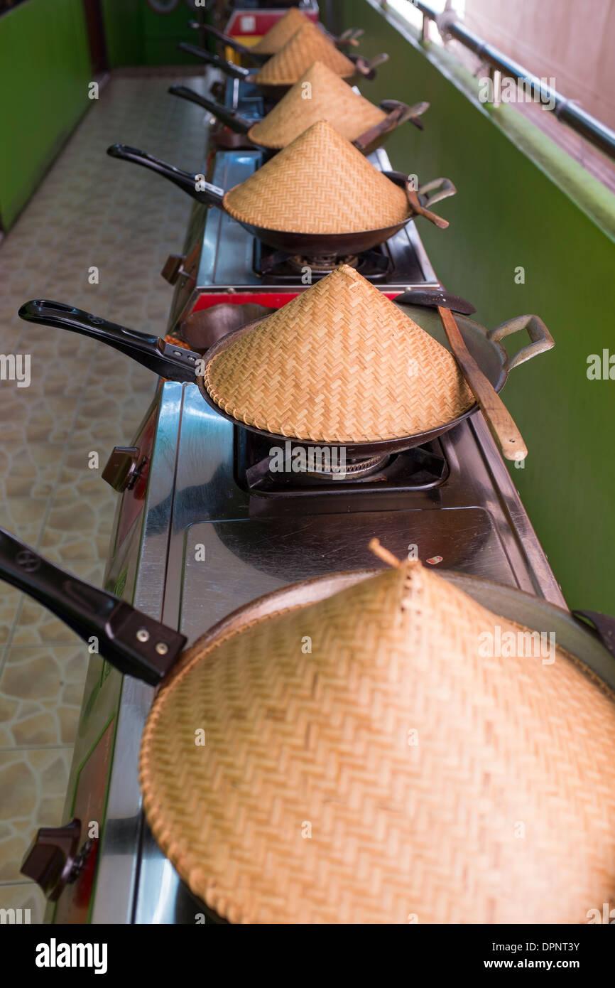 Woks on Stoves at Silom Cookery School - Stock Image