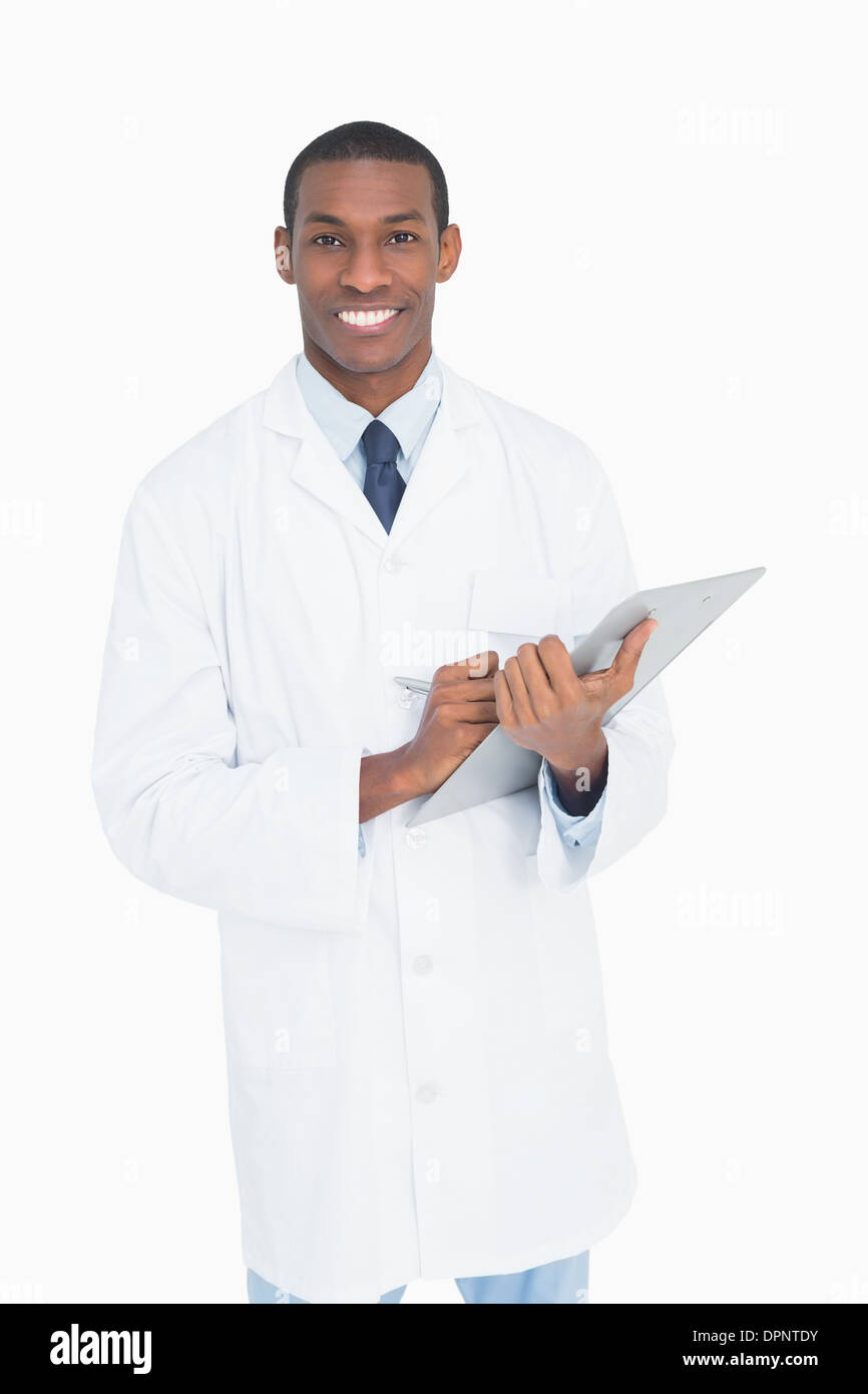 Portrait of a smiling male doctor with clipboard - Stock Image