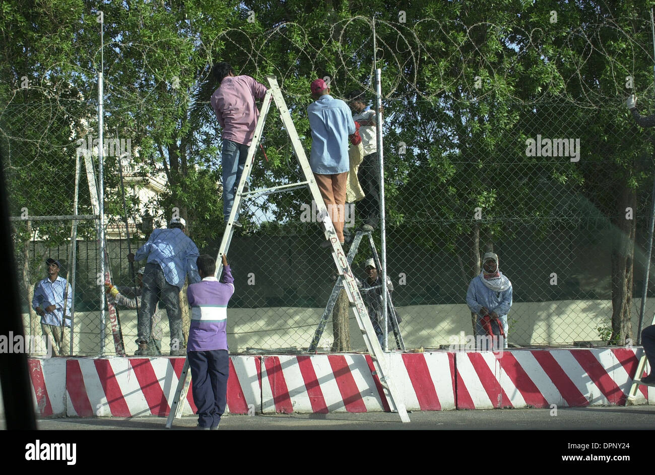 Workers installing barbed wire and other security measures on the perimeter of a compound housing foreigners and westerners. - Stock Image