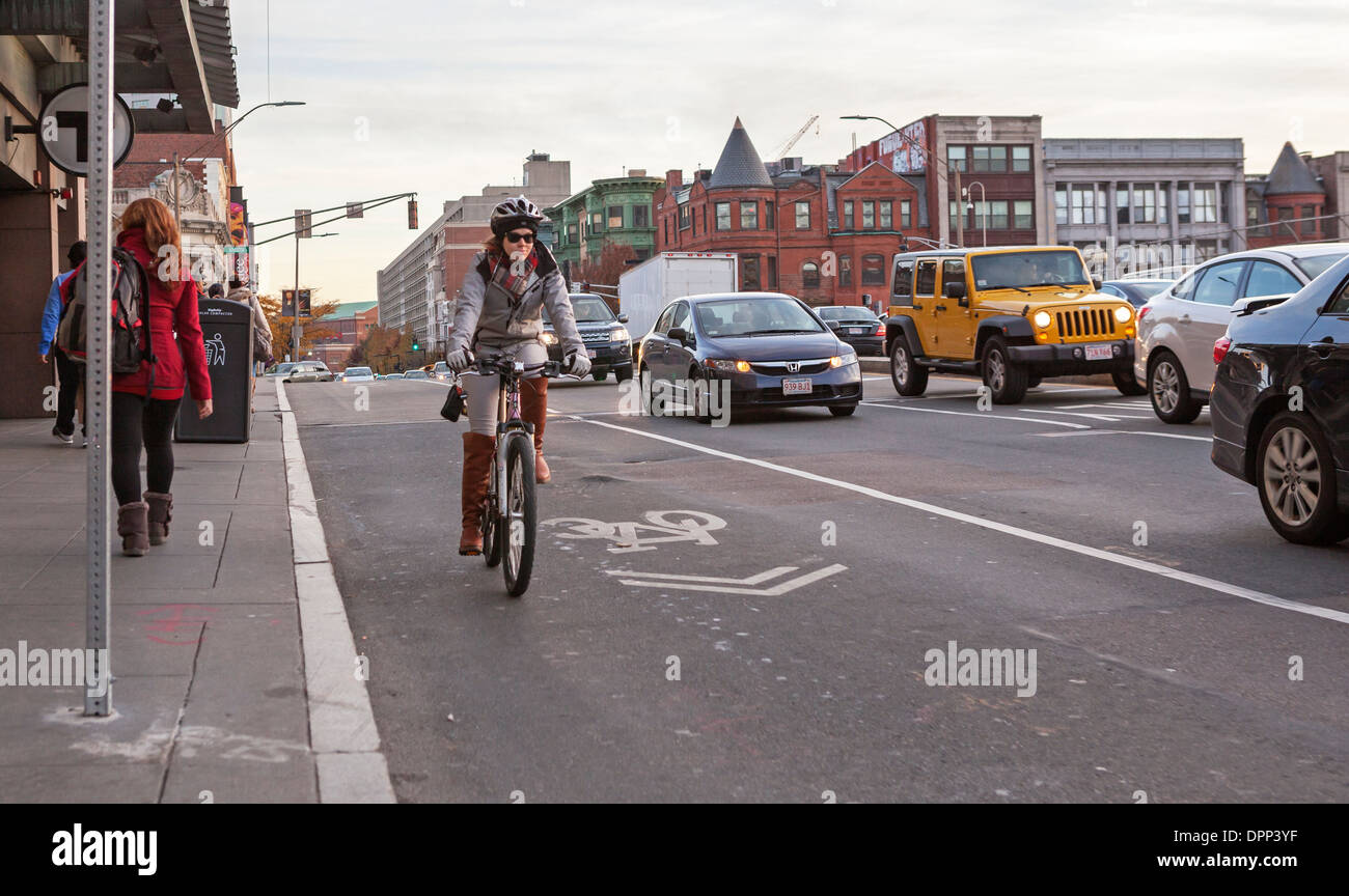A woman rides her bicycle in a designated bike lane in Boston. - Stock Image