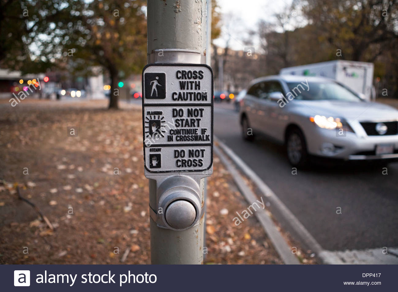 A pushbutton and sign help pedestrians to cross the street safely in Boston. - Stock Image