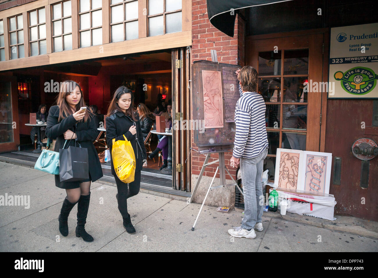 A man draws art on his easel on Newbury Street in Boston as two women pass by. - Stock Image