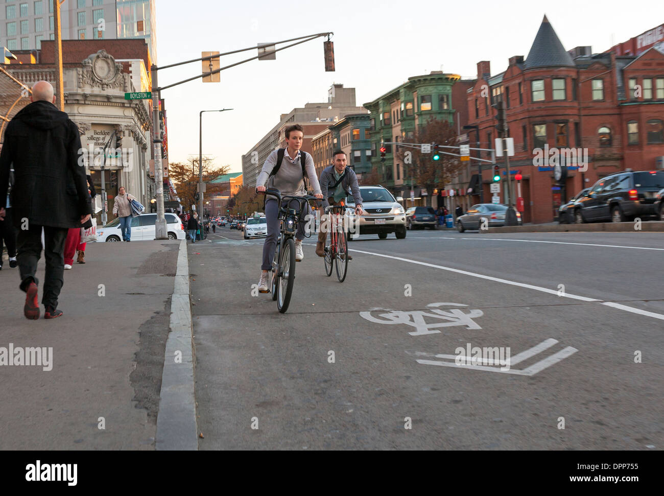 A man and woman ride their bicycles in a bike lane in Boston. - Stock Image