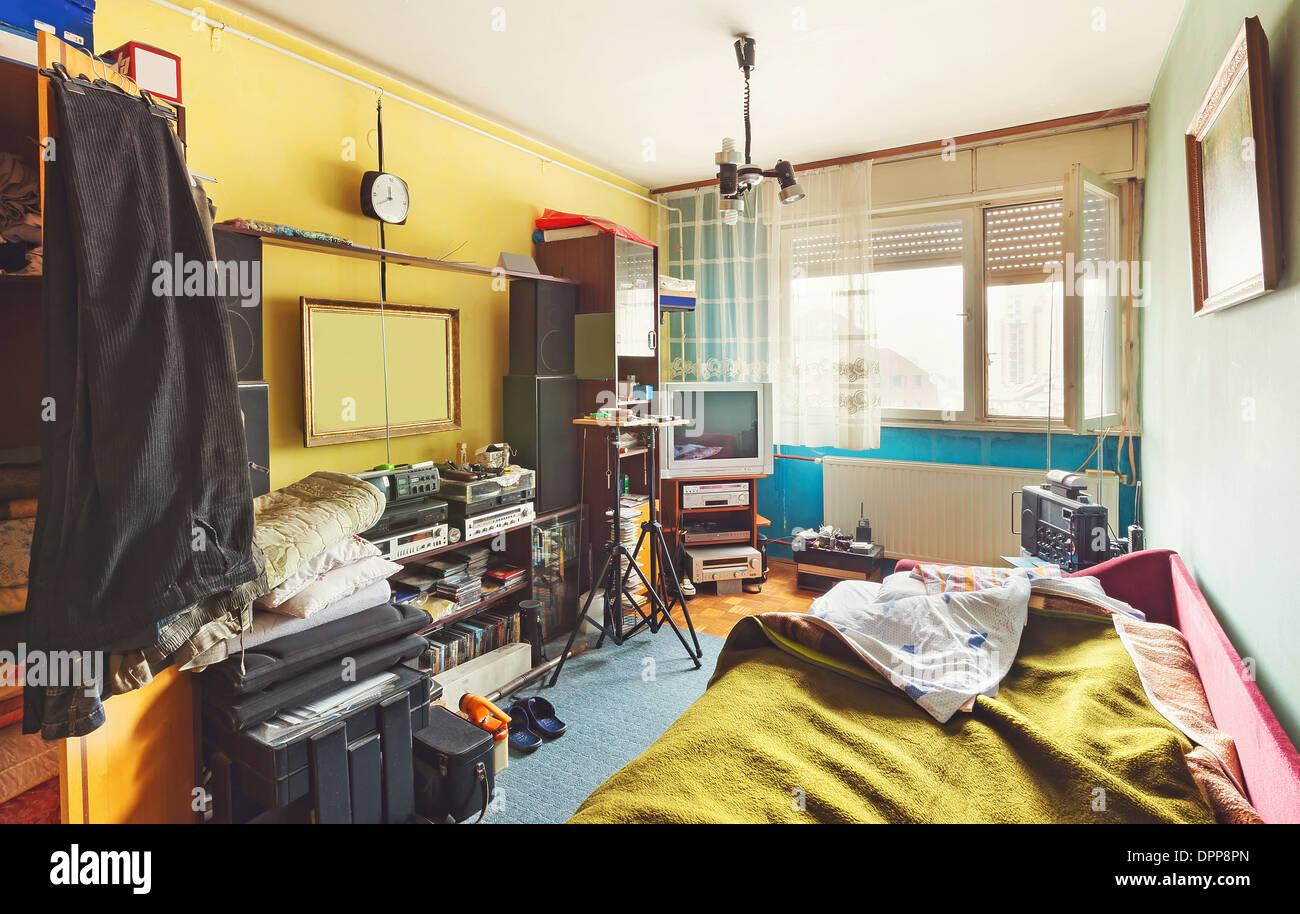 Messy room interior, a lot of different stuff, from electronic appliances and furniture to clothes. - Stock Image