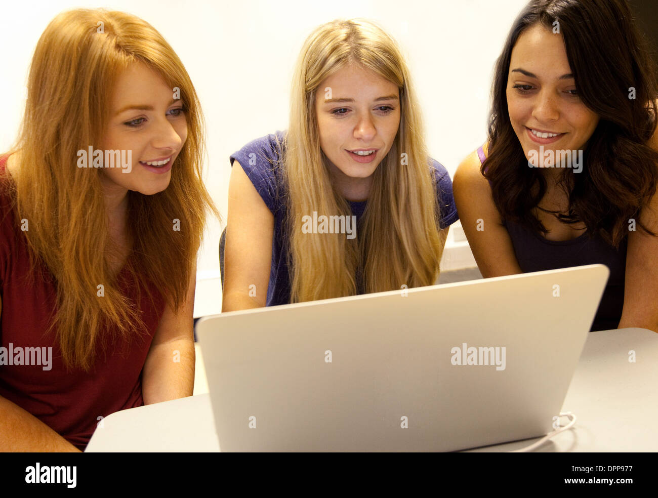 Three girls looking at a laptop computer, Essex UK - Stock Image